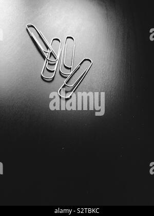 Steel wire paper clips laying on office desk. - Stock Photo