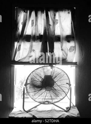 Floor fan sitting on window on a hot and sunny day. - Stock Photo