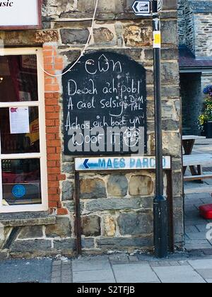 Welsh language sign: 'Dogs, bring your humans.  Get a free sausage - because you're woof it!'  On a cafe in Cardigan, Wales. - Stock Photo
