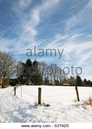 Snow covered field in winter and fence against blue sky with clouds - Stock Photo