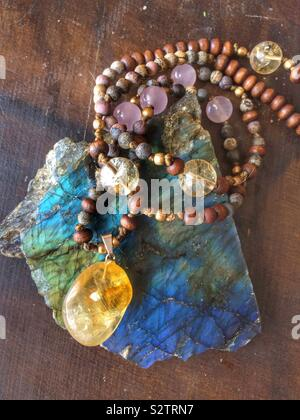 Jewelry necklace on raw labradorite mineral stone - Stock Photo