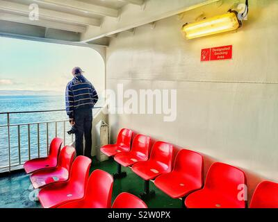 Man standing alone on deck of ferry near rows of empty red plastic seats, Inner Hebrides, Scotland - Stock Photo