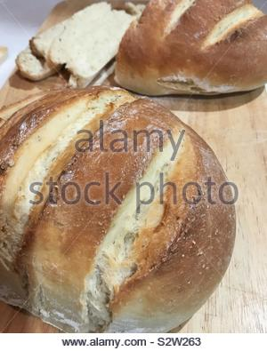 Freshly baked homemade bread on wooden cutting board - Stock Photo