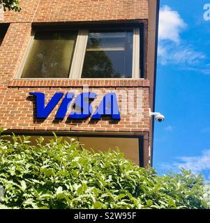 VISA sign on red brick office building - trademark symbol of the credit card company - banking, ecommerce and electronic transactions - Visa Europe, Queens Road, Reading, United Kingdom - Stock Photo