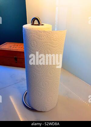 Paper towels on the kitchen counter dispensed by a metal spindle paper towel holder - Stock Photo
