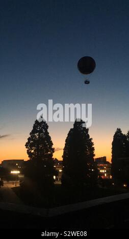 Hot air balloon above Disneyland Paris at sunset - Stock Photo