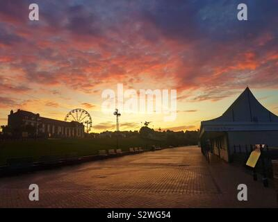 Dawn breaking over Barry Island funfair and promenade, South Wales. - Stock Photo