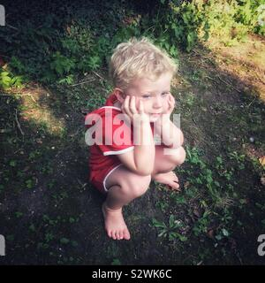 Three year old boy waiting patiently in the garden. - Stock Photo