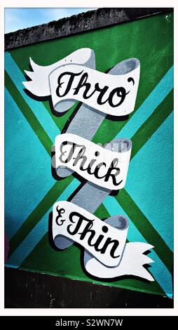 A section of a street art wall mural in Bristol, UK, with the words 'Thro' Thick & Thin' - Stock Photo