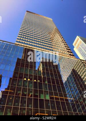 Reflections of skyscrapers on the glass façade of 300 Madison Ave. headquarters for Price Waterhouse Coopers LLP accounting firm at 42nd St. in Midtown Manhattan, NYC, USA - Stock Photo