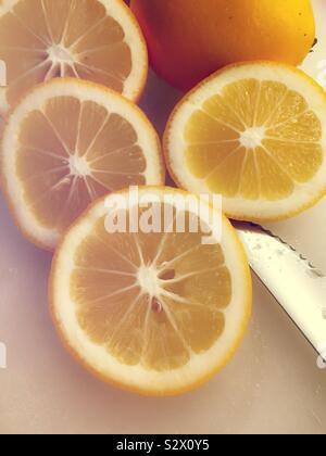 Slices of a fresh Meyer lemon on a cutting board with a knife, USA - Stock Photo