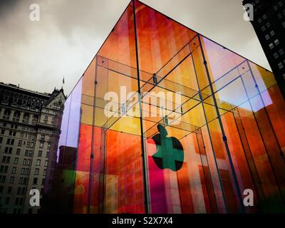 The iconic Apple store glass cube is located across from the famous plaza hotel in wrapped in a temporary iridescent wrap, NYC, USA - Stock Photo