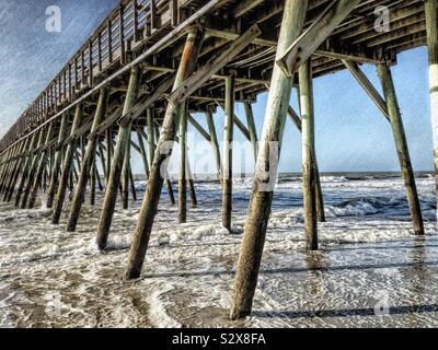 A wooden pier in Myrtle Beach South Carolina on the Atlantic Ocean. This image has a vintage grunge textured effect. - Stock Photo