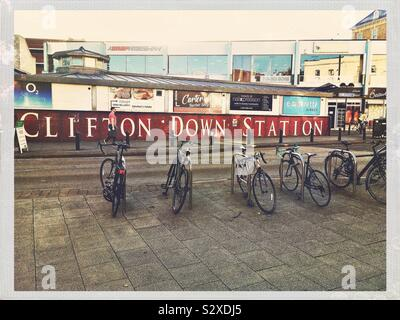 A large panelled metal sign for Clifton Down Station, in dark red with cream capital letters. The sign is on Whiteladies Road and there are parked bicycles on the nearer side of the street. - Stock Photo