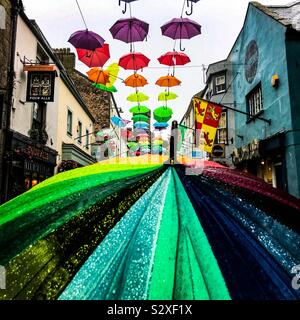 Looking over the top of a pedestrian carried colourful umbrella up Palace Street in Caernarfon North Wales at the 170 brolly art installation by Hwb Caernarfon - Stock Photo