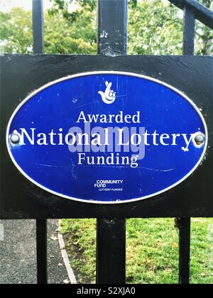 A blue and white, oval sign on a park gate, saying 'Awarded National Lottery Funding' - Stock Photo