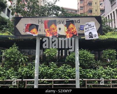 A road sign is plastered with V For Vendetta-inspired anti-government messages, in Causeway Bay, Hong Kong. - Stock Photo