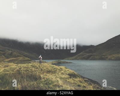 Woman in hiking clothing looking over lake in front of misty mountains - Stock Photo