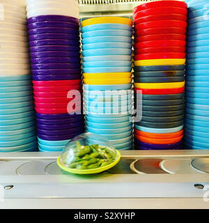 Bowl of green edamame beans on a sushi restaurant conveyor belt carousel. - Stock Photo