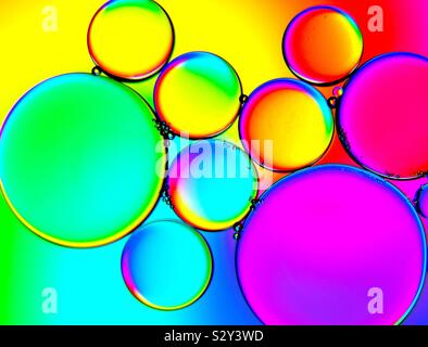 Bubbles of oil floating on water above a colourful gradient background - Stock Photo