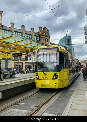 Metro link tram at Exchange Square tram stop in Manchester - Stock Photo