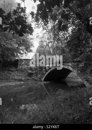 Arched stone bridge over river in black and white. - Stock Photo