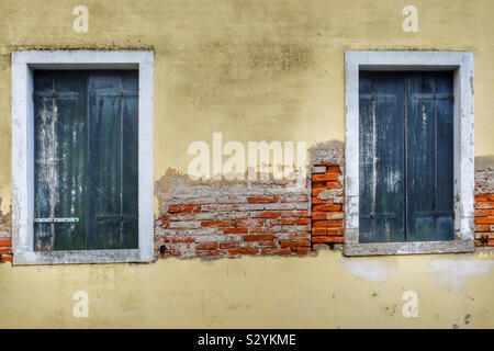Two green wooden doors with a wall with chipped plastered brick wall in between - Stock Photo