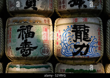 Sake barrels used to store alcoholic drink stacked outdoors in natural lighting covered in Japanese designs and symbols
