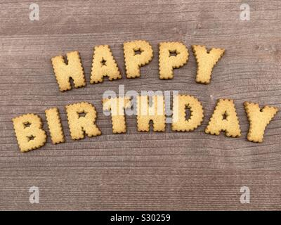 Happy Birthday text with biscuit letters on a wooden board - Stock Photo