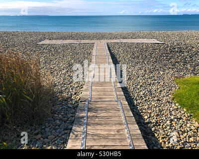 Wooden boardwalk over the pebbles at Newgale Beach, Pembrokeshire, Wales in the Pembrokeshire Coast National Park. - Stock Photo