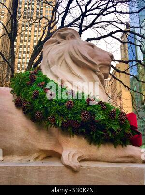 Fortitude one of the two library liens on fifth Avenue has his holiday wreath in a seasonal celebration, NYC, USA - Stock Photo