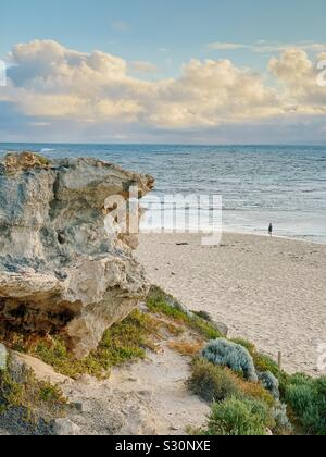 Lone woman walking at sunset on the beach at Surfers Point, Prevelly, Western Australia. November 2019. Rocky outcropping in foreground. - Stock Photo