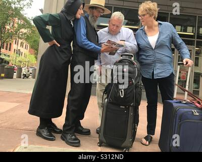 Mennonites ask for directions at Union Station in Downtown Denver. - Stock Photo