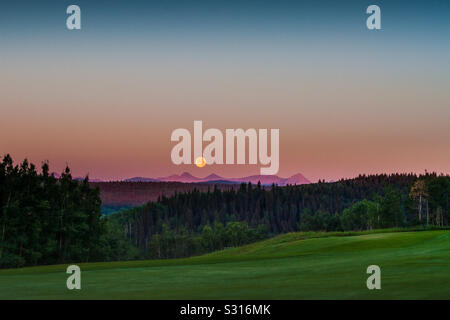 Moon setting over Rocky Mountains - Stock Photo