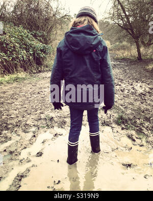 Thoughtful child in water and mud. Girl aged age 7 years stuck in a muddy puddle well wearing Wellington boots. - Stock Photo