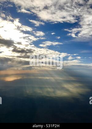 The sun's rays shine through a layer of cloud and ignite the earth below. - Stock Photo