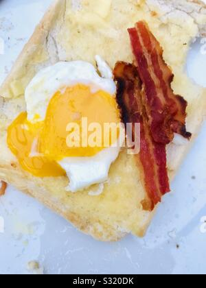 Eating bacon and fried egg on thick white sliced toast - Stock Photo