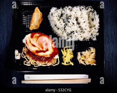 Japanese bento lunch with hamburger, egg, noodles, rice, and pickes on a plastic try - Stock Photo