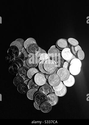 Heart shaped coins piled up to take pic in black background - singapore coins  wealth in abundance- a valuable heart - Stock Photo