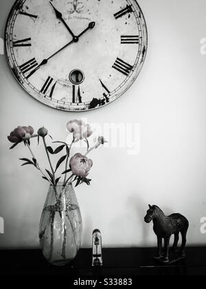 A black and white still life photograph of a clock, oriental horse ornament, metronome and a vase of peony flowers, all placed on a piano. - Stock Photo
