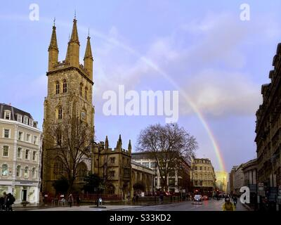 UK Weather: A rainbow shines over Christchurch Greyfriars Church, in the evening dusk on Holborn Viaduct, London, England. - Stock Photo