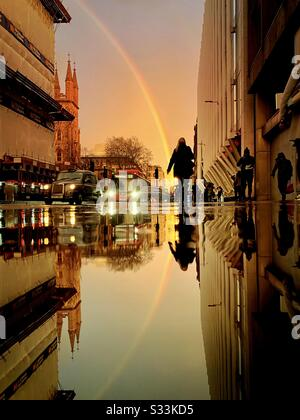 UK Weather: A rainbow shines over the Walkie Talkie building, as it is reflected on a rainy street in Holborn Viaduct, London, England. - Stock Photo
