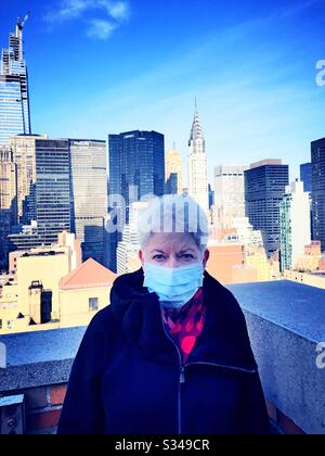 Elderly woman with health and safety concerns wears a protective facemask in midtown Manhattan during the COVID-19 pandemic, New York City, USA