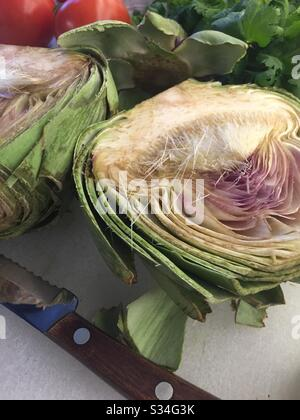 Close up of a cut in half large artichoke on a residential kitchen cutting board, USA - Stock Photo