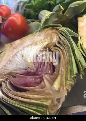 Still life of a cut in half artichoke and other vegetables on a cutting board in a residential kitchen, USA - Stock Photo