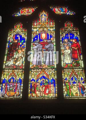 Stained glass window depicting the burial of King Edward II at Gloucester Cathedral in England. - Stock Photo