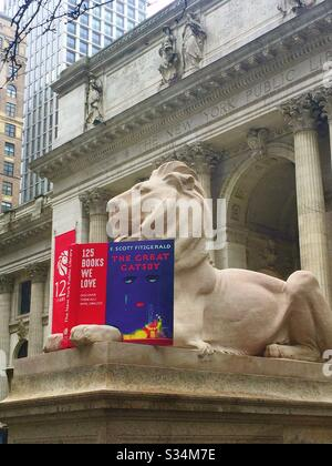 Fortitude the New York public library lion statue and a display to encourage participation in reading month of February, NYC, USA - Stock Photo