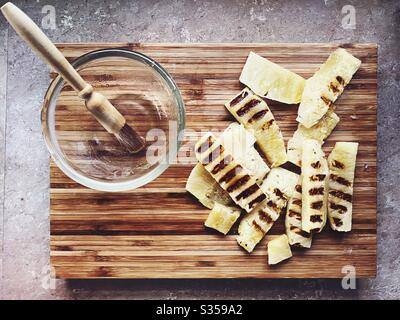 Preparing dinner in the kitchen. Fresh food preparation. Ingredients for homemade pineapple salsa. Chargrilled slices on a wooden chopping board and honey marinade
