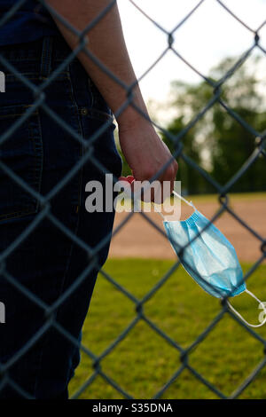 Young man holding a face mask behind a chain link fence at a baseball park. - Stock Photo