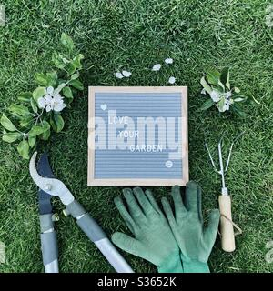 Love your garden. Gardening concept with felt letter board, handheld prune, dirty gloves and a pruned branch with blossom from an apple tree on a green lawn - Stock Photo